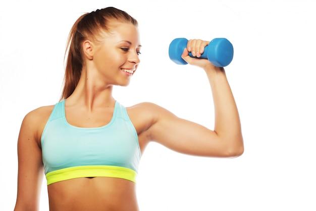 Vrouw in sportuitrusting praktijk met handgewichten, geïsoleerd op wit