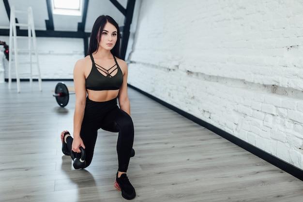 Vrouw in sportuitrusting praktijk met handgewichten geïsoleerd op zwart.