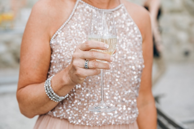 Vrouw in sprankelende roze jurk houdt glas champagne in haar ar