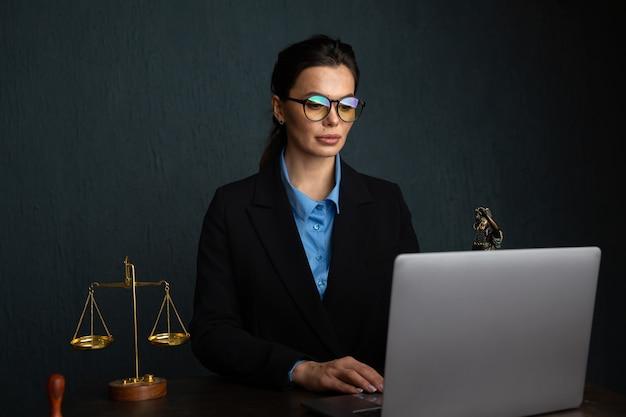 Vrouw in stijlvolle bril notaris schrijven in leerboek tijdens online leren op laptopcomputer