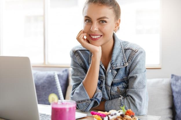Vrouw in stijlvolle denim jasje in coffeeshop