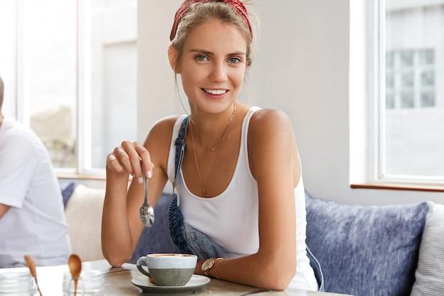 Vrouw in stijlvolle denim overall in coffeeshop