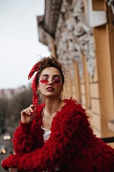 Vrouw in stijlvolle jas en rode bril poseren op balkon