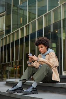 Vrouw in stijlvolle kleding gebruikt moderne mobiele telefoon om online te chatten updates applicatie poseert buiten tevreden goede internet looks met serieuze expressie poses in stedelijke stad