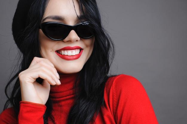 Vrouw in stijlvolle zonnebril glimlachend en wegkijken