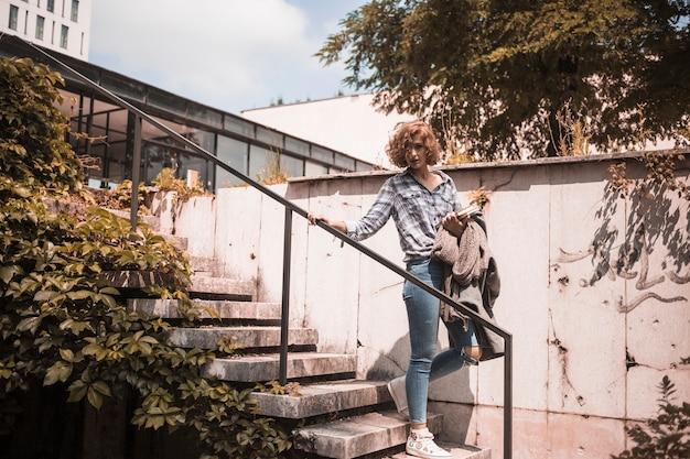 Vrouw in straatkleding die op stappen daalt