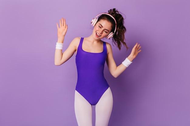 Vrouw in strakke kleurrijke kleding voor fitness luistert naar energieke muziek in koptelefoons en dansen op paarse muur