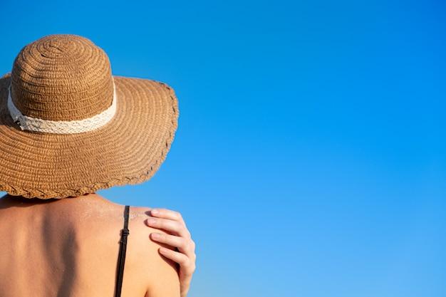 Vrouw in strand hoed, bedekt met zand op heldere blauwe achtergrond.