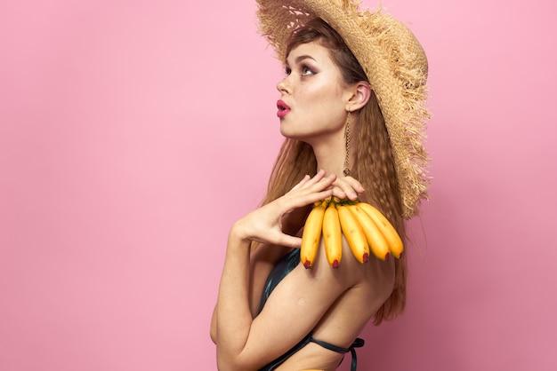 Vrouw in strand strohoed bananen met fruit