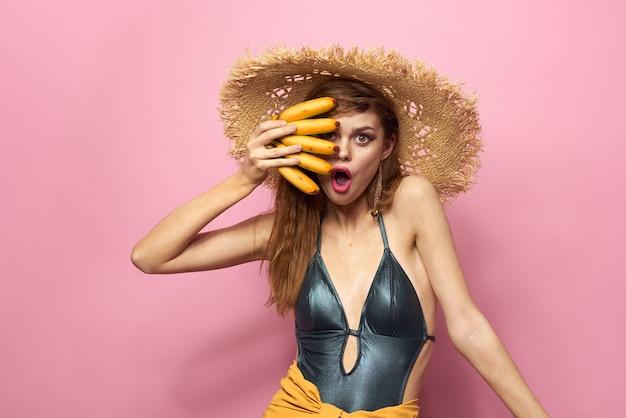 Vrouw in strand strooien hoed bananen met fruit exotische zwembroek roze achtergrond