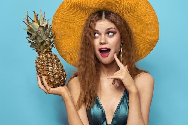 Vrouw in strandhoed ananas met zwembroek exotische vruchten blauwe achtergrond vakantie