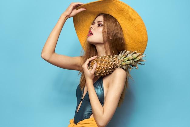 Vrouw in strandhoed ananas met zwembroek exotische vruchten blauwe vakantie