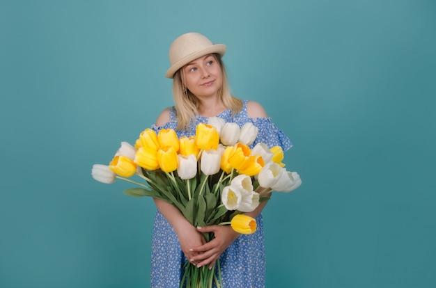 Vrouw in strohoed die blauwe kleding met witte en gele tulpen in haar handen draagt. zomer en lente concept.