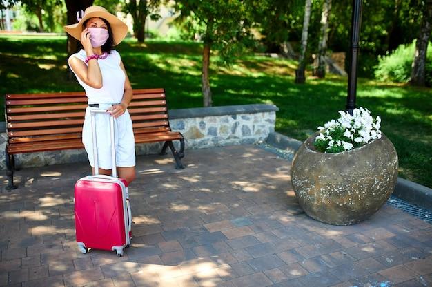 Vrouw in strohoed en roze beschermend masker, in het park buiten met een koffer, praten op een mobiel, leven tijdens coronavirus pandemie, vliegreizen openen, reisconcept.