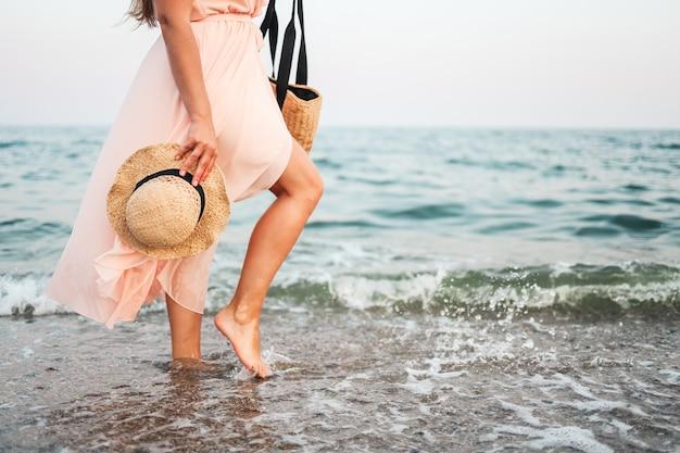 Vrouw in strohoed en roze jurk op een tropisch strand met bruine tas.