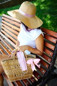 Vrouw in strohoed en tas met roze beschermend masker, zittend op de bank in het park buiten in de stad, concept zelfzorg, leven tijdens coronavirus pandemie, covid-19