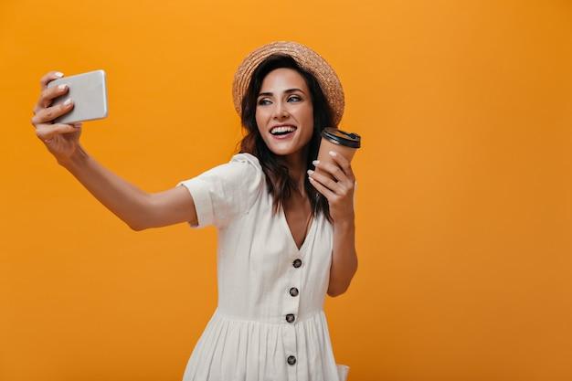 Vrouw in strohoed en witte jurk maakt selfie op smartphone en houdt glas thee. volwassen dame in lichte outfit neemt foto met koffie in haar handen.