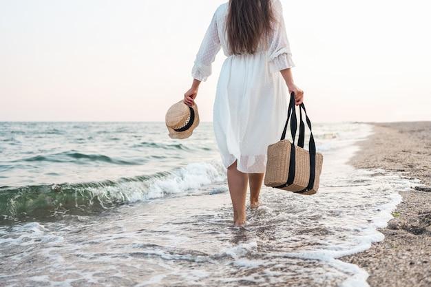 Vrouw in strohoed en witte jurk op een tropisch strand met bruine tas.