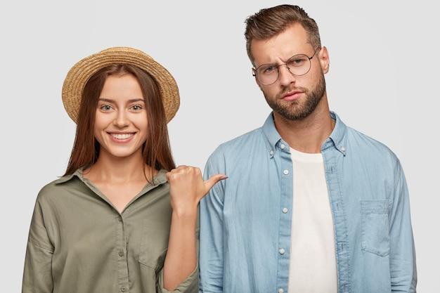 Vrouw in strohoed heeft een brede stralende glimlach, wijst naar haar vriend die een ontevreden uitdrukking heeft, brengt samen vrije tijd door, poseert tegen de muur