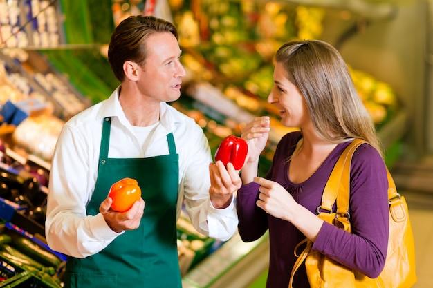 Vrouw in supermarkt en winkelbediende