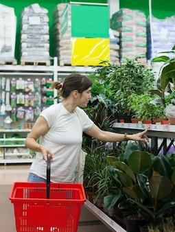 Vrouw in supermarkt in de buurt van afdeling met bloemen binnen