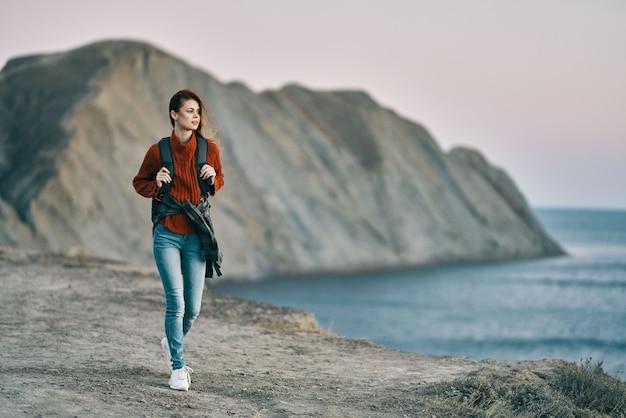 Vrouw in sweaterjeans en sneakers aan de kust en de bergen