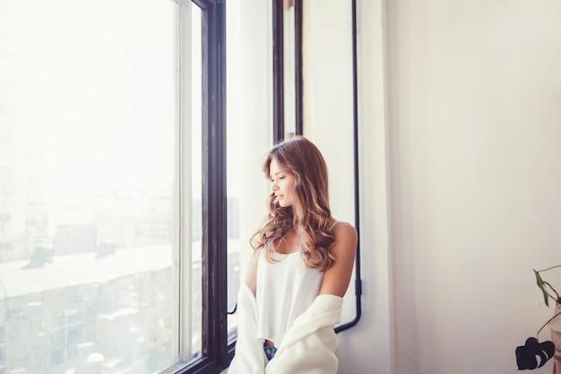 Vrouw in t-shirt dichtbij venster