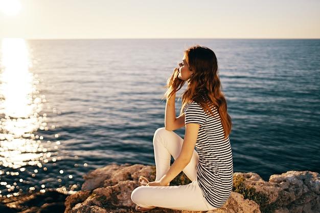 Vrouw in t-shirt en broek portret zee zonsondergang zon