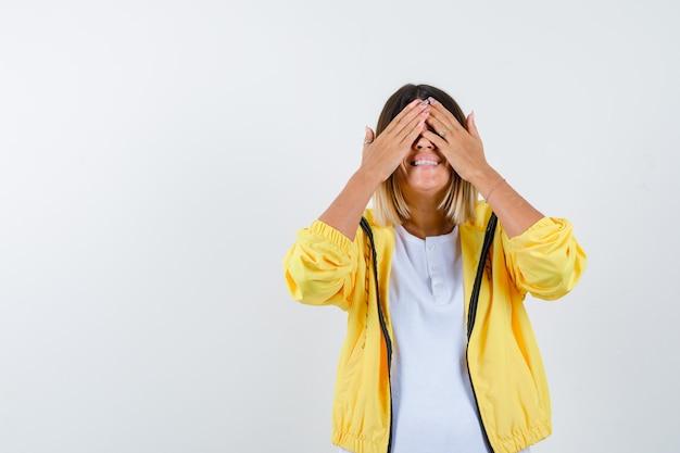 Vrouw in t-shirt, jas die handen op de ogen houdt en gelukkig, vooraanzicht kijkt.