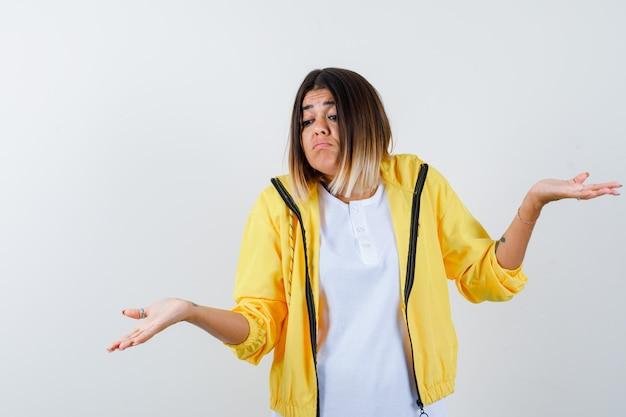 Vrouw in t-shirt, jasje met hulpeloos gebaar en op zoek naar verward, vooraanzicht.