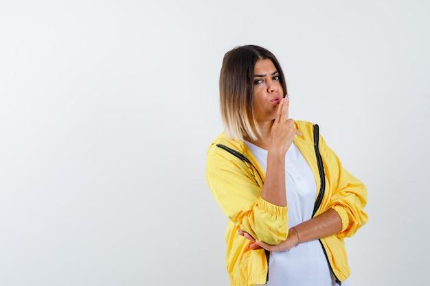 Vrouw in t-shirt, jasje met pistoolgebaar en op zoek naar zelfverzekerd, vooraanzicht.