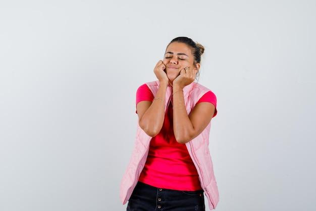 Vrouw in t-shirt, vest dempt gezicht op haar handen en ziet er hoopvol uit