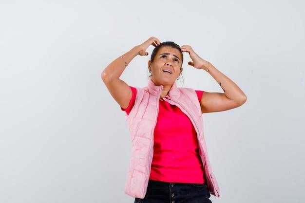 Vrouw in t-shirt, vest hand in hand op hoofd en depressief?