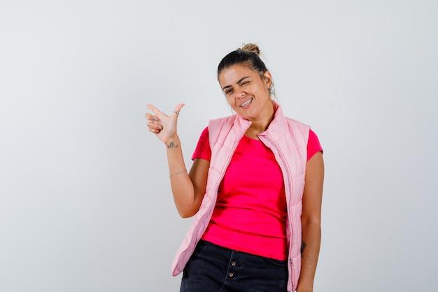 Vrouw in t-shirt, vest maakt vingerpistoolteken en ziet er zelfverzekerd uit