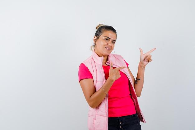 Vrouw in t-shirt, vest met geweergebaar en vrolijk kijkend