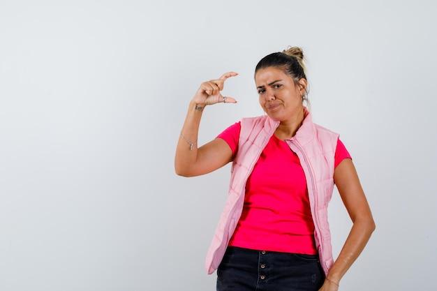 Vrouw in t-shirt, vest met klein bordje en aarzelend