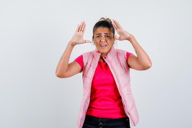 Vrouw in t-shirt, vest met opgeheven handen bij het hoofd en verbaasd kijkend