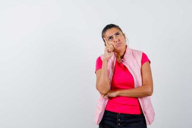 Vrouw in t-shirt, vest staat in denkende houding en kijkt aarzelend