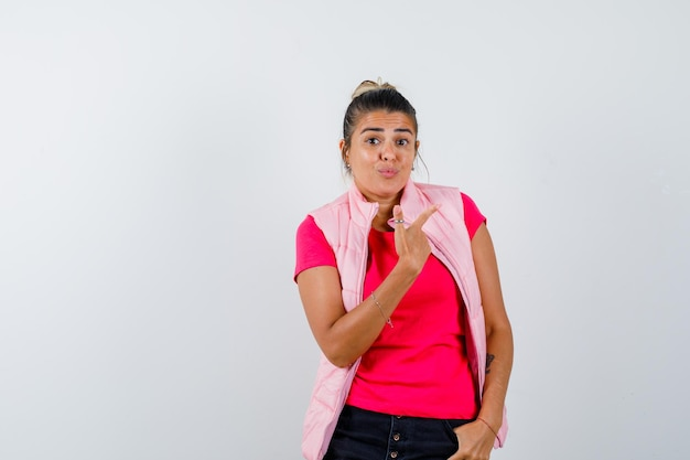 Vrouw in t-shirt, vest wijzend naar de rechterbovenhoek en aarzelend