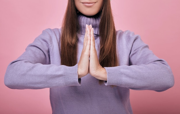 Vrouw in tedere paarse trui bidden