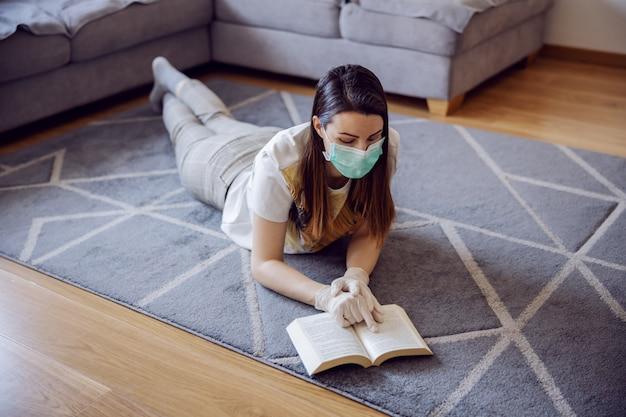 Vrouw in thuisisolatie met gezichtsmasker en handschoenen, leest een boek en bestudeert informatie over coronavirus outbrake 2020. thuisonderwijs tijdens quarantaine.