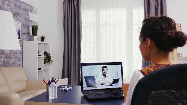 Vrouw in tijd van videooverleg met haar arts.