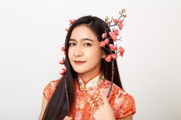 Vrouw in traditionele chinese rode kleding met pruimbloemen