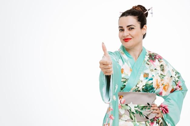 Vrouw in traditionele japanse kimono blij en blij met duim omhoog op wit
