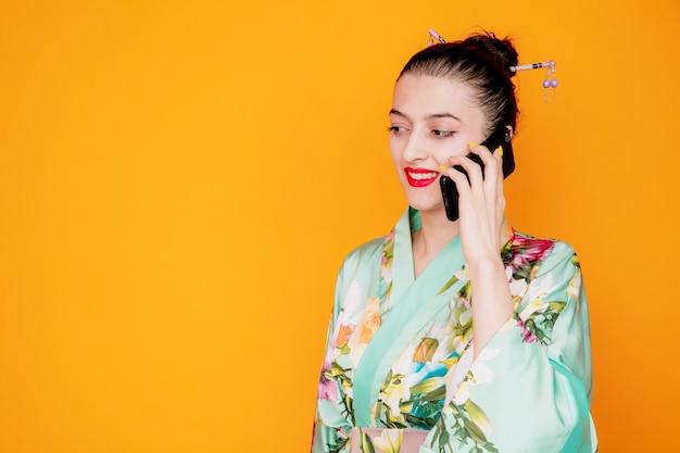Vrouw in traditionele japanse kimono blij en positief glimlachend terwijl ze op de mobiele telefoon op oranje praat