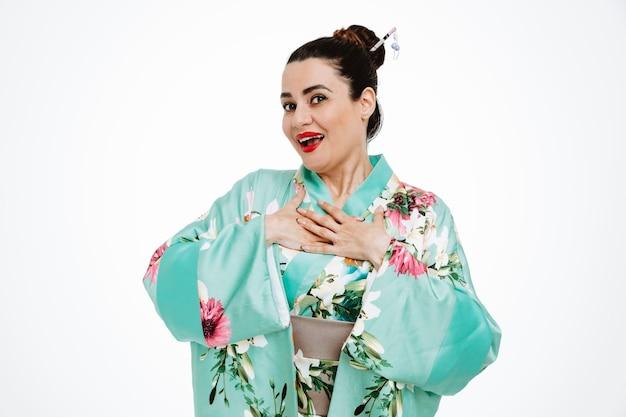 Vrouw in traditionele japanse kimono, blij en vrolijk, hand in hand op haar borst, dankbaar op wit