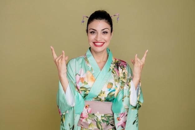 Vrouw in traditionele japanse kimono blij en vrolijk met rotssymbolen op groen