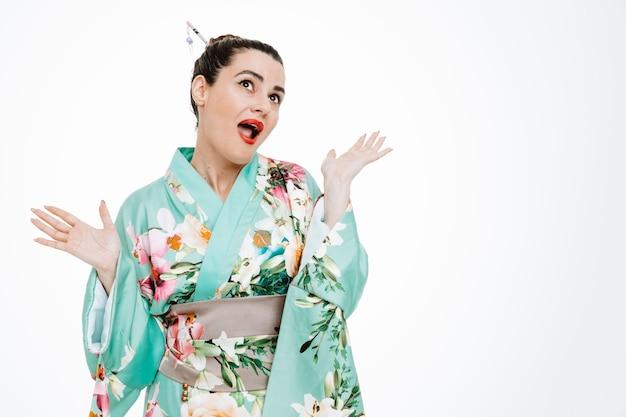 Vrouw in traditionele japanse kimono die blij en verbaasd opkijkt en armen op wit steekt