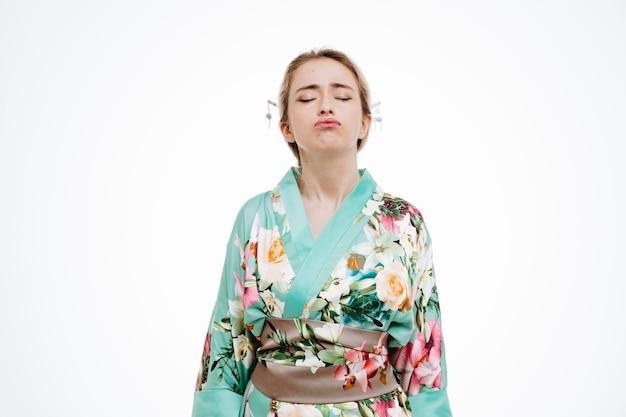 Vrouw in traditionele japanse kimono die er moe en geïrriteerd uitziet en wangen blaast met gesloten ogen op wit