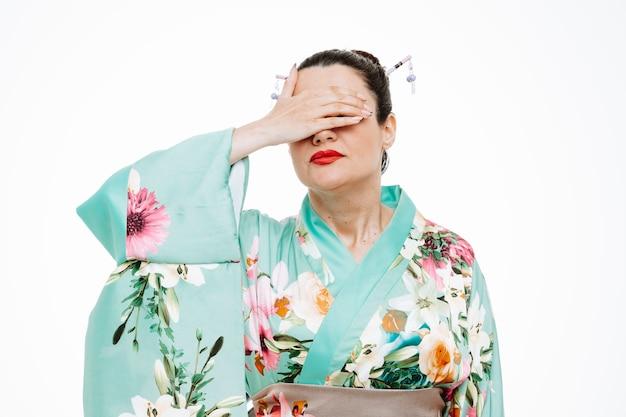 Vrouw in traditionele japanse kimono die er moe en verveeld uitziet met gesloten ogen met een hand op wit